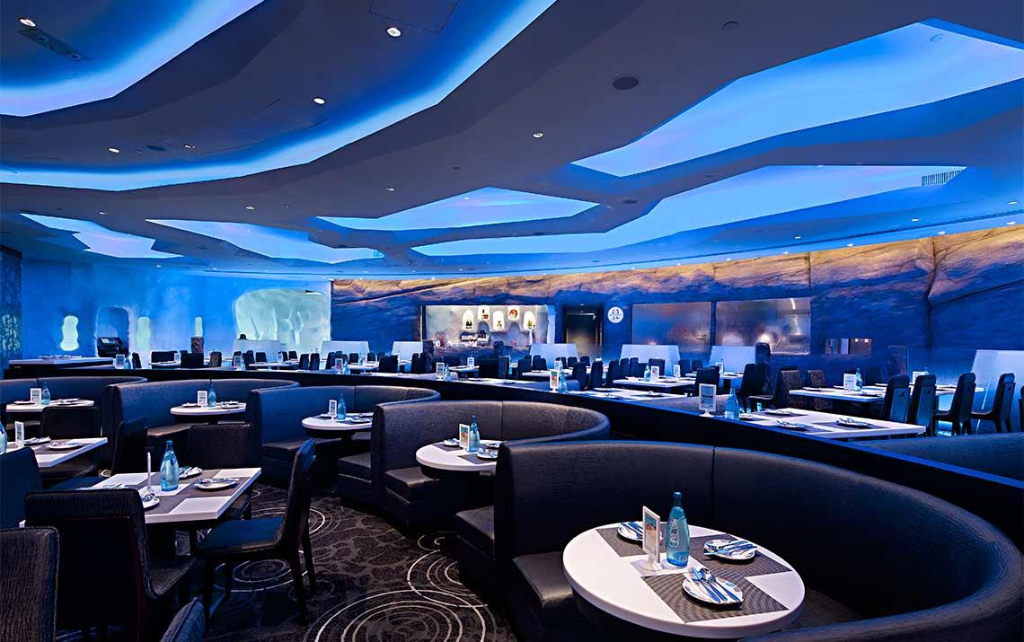 主要餐区  餐厅由三个主要部分组成:酒吧、用餐区和一个开放式厨房。酒吧区的柜台用来给游客配发饮料。开放式厨房为游客营造一种友好、愉快、有趣的氛围。用餐区上、下两层的设计,能让游客清晰地看到餐厅内的所有景象。 首先,两层空间的设计理念旨在帮助游客能够清晰观赏到整体景致及企鹅的一举一动,玻璃天花板营造出海洋氛围,尤其在日光映照的瞬间,整个餐厅范围内都波光粼粼,水影荡漾,自然与环境相融,仿佛是置身于南极海底世界.