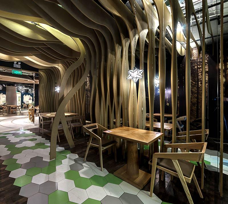 """餐厅入口空间营造了高密度的雨林带,用""""蜂巢""""铺出动线,在神秘的森林回"""