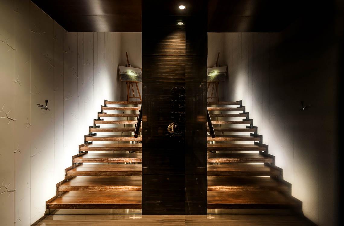 对称的中式木质楼梯用墙柱隔开在优雅的灯光下连