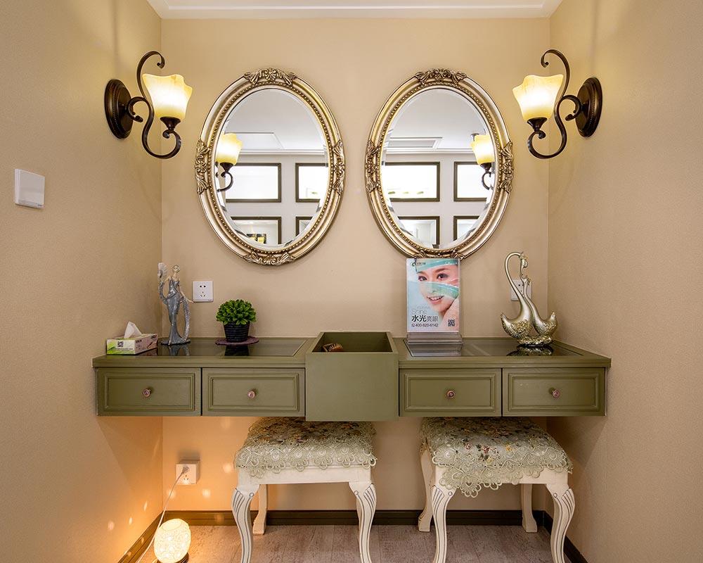 低调的抹茶绿梳妆台,金色镶花的椭圆镜面,完美弧线的方凳,曼妙的壁灯